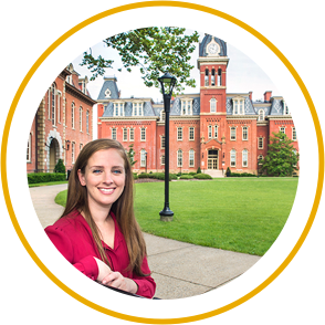Girl in Corporate attire standing at the front view of WVU Building