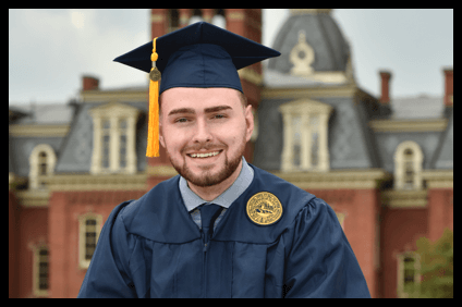 Male college graduate in a cap and gown smiling in front of West Virginia University's campus.